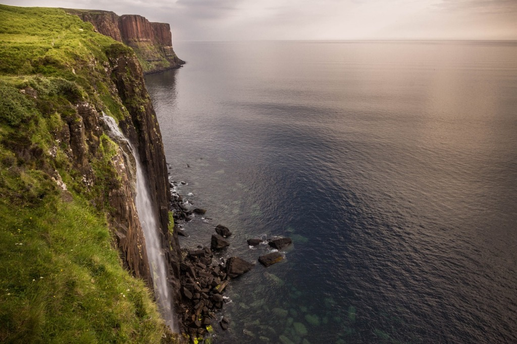 Sea cliffs with waterfall on a cloudy day on the Isle of Skye.