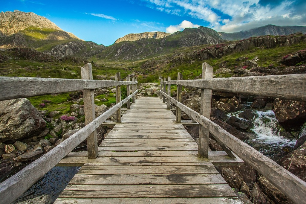 Looking along a wooden bridge over a stream towards the hills of Snowdonia.